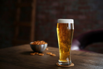 Glass of light beer with snacks on wooden table