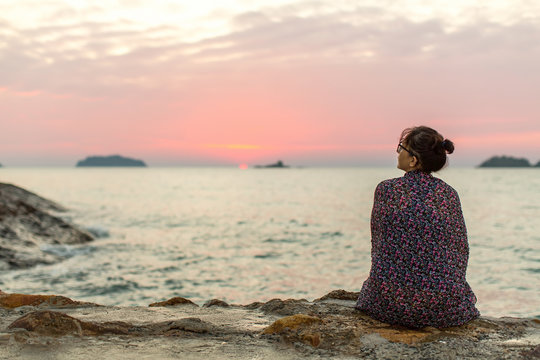 Lonely woman sitting on the seashore after sundown.