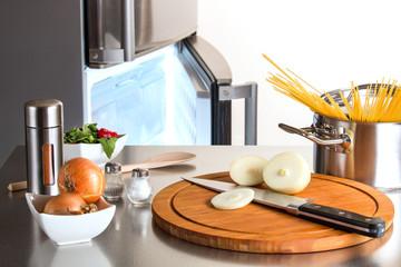 Zwiebeln, Spaghetti und Gewurze vor geöffnetem Tiefkühlfach eines Kühlschrankes