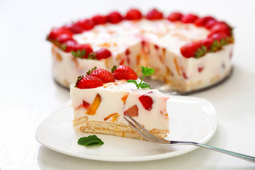 Cake with strawberries, gelly yogurt and cherries. Surface view. Isolated on white background. One piece in a white plate