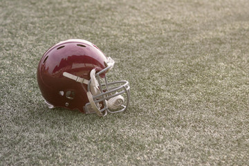 Football helmet lying on green grass field