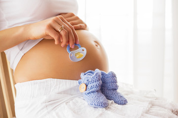 Pregnant woman holding baby shoes and pacifier