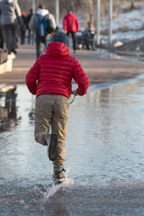 A boy in a red jacket on a scooter in a park in early spring. Sunny spring day. Splash in a puddle on a scooter