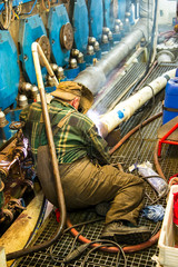 Welder during the repair welding of the pipeline in the engine room of the ship