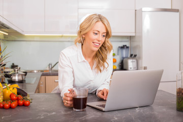 Woman working on computer while drinking coffee in kitchen