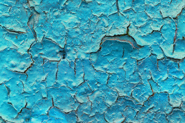 Close-up of a turquoise paint peeled off of a wall texture background.