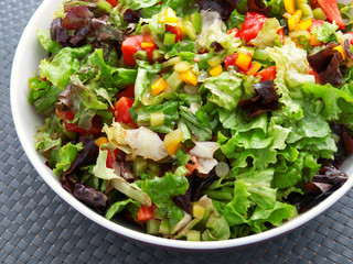 Green salad with tomatoes and peppers. Vertical shot, high angle view