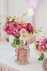 Маленький розовый букет на праздничном столе с рамкой для фотографий