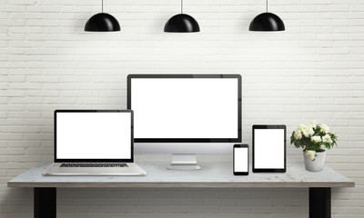 Devices on desk with isolated screen for mockup. Computer display, laptop, tablet and smart phone on office desk. Flowers, lamps and brick wall in background