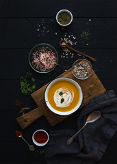 Pumpkin soup with cream, seeds and spices in rustic metal bowl over grunge black background. Top view.