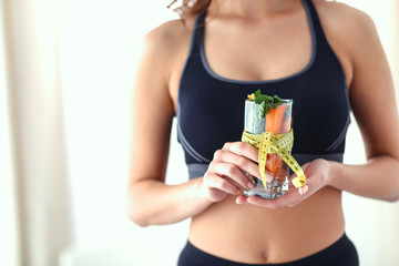 Woman holding a drinking glass full of fresh fruit salad with a tape measure around the glass