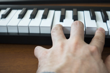 Hand Playing Notes on an Electronic Keyboard