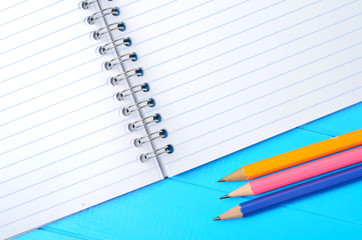 Empty notebook with pencils