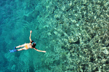 Woman snorkeling in crystal clear tropical water