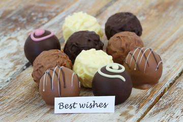 Best wishes card with assorted pralines and truffles on rustic wooden surface