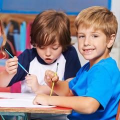 Kinder malen Bilder mit Pinsel im Hort