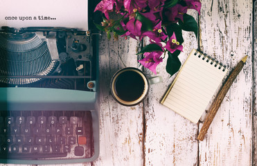 "image of vintage typewriter with phrase ""once upon a time"", blank notebook, cup of coffee on wooden table"