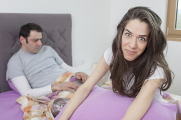 Angry woman sitting in bed, couple is fighting because he's working too much