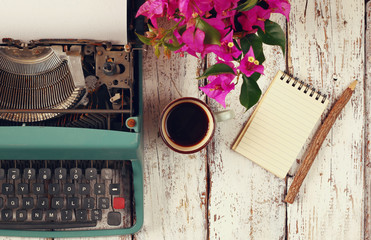 image of vintage typewriter, blank notebook, cup of coffee on wooden table