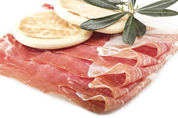 Italian prosciutto crudo ,raw ham leg sliced on white