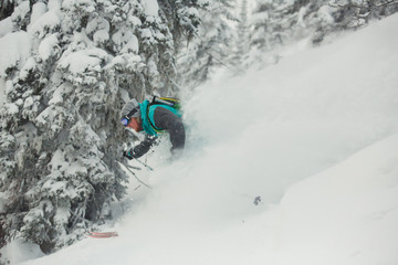 Extreme downhill skier on the snow in forest.