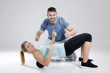 Trainer und Sportlerin bei Sportübung