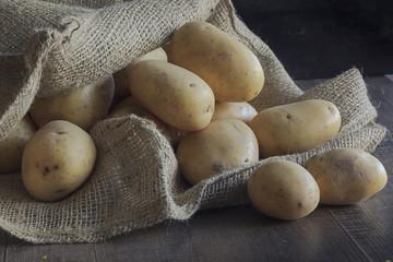 Kartoffeln in einem Juteack mit dunklem Hintergrund