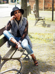 Spring outfit - beautiful smiling african italian woman with granny hairstyle, ripped jeans, hig heels sandals, lace shirt, black hat, leather bag and fur vest.