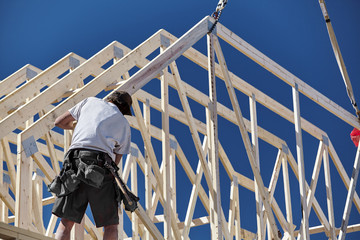 Construction carpenter man setting roof trusts into place