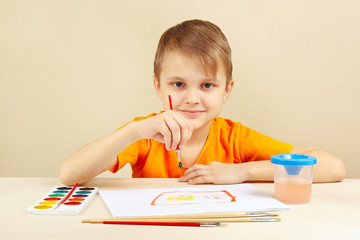 Little boy in an orange shirt painting with watercolors