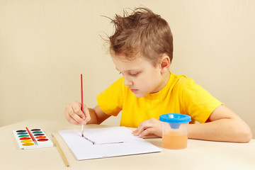 Little artist in a yellow shirt painting colors