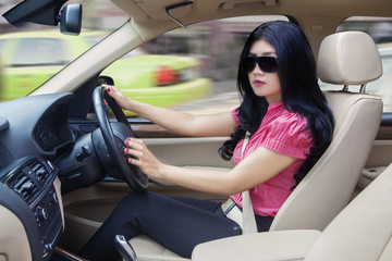 Woman with sunglasses driving new car