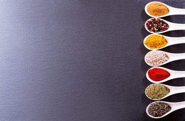 various spices in ceramic spoons on dark background