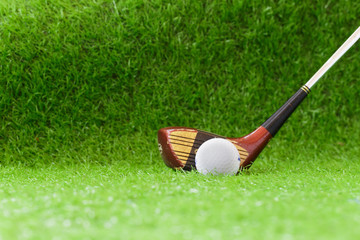 Old golf club and golf ball on green grass background.Outdoor sport concept.