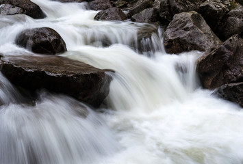 Small water fall with water pouring over rocks. Long exposure