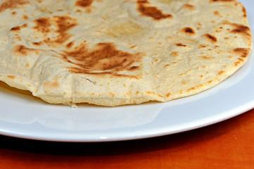 Homemade whole-wheat flour tortillas on a white plate