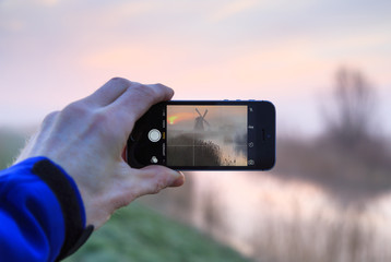 Male hand using a smartphone to take a photo of a sunrise at a windmill in Holland.