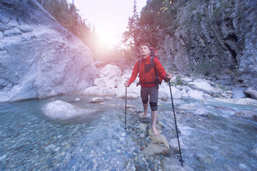 Young man with a backpack to move a mountain river.