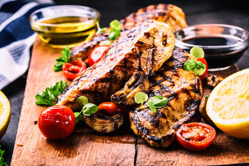 Grilled chicken breast in different variations with cherry tomatoes, .mushrooms, herbs, cut lemon on a wooden board or teflon pan. Traditional cuisine. Grill kitchen.