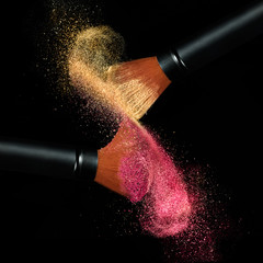 Makeup brushes applying powder isolated on black