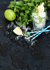 Mojito cooking set. Bunch of fresh mint, lime, chipped ice and coctail glass over black slate stone backdrop