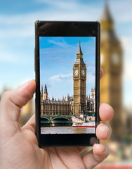 Tourist holds smartphone in hand and photographing Big Ben in London.