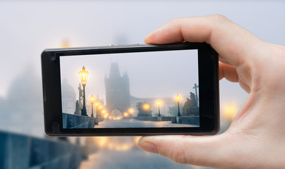 Tourist is photographing Charles Bridge in Prague with smartphone.
