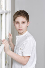 A young boy on a background framed windows