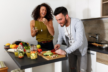 Young couple in kitchen preparing together vegetarian meal.Preparing fruit salad.