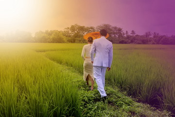 couple of women and man with Thai traditional dress walking on p