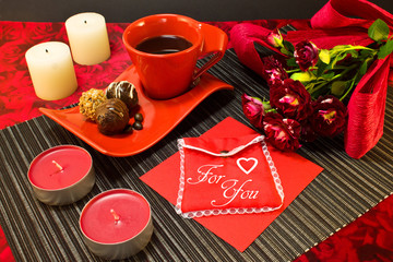 Coffee in red cup with gift envelope