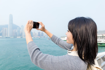 Woman take photo of victoria harbor in Hong Kong