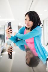 Woman using mobile phone to take selfie