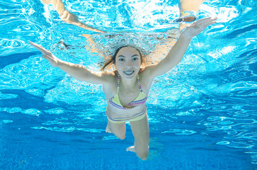 Child swims in pool underwater, happy active girl dives and has fun under water, kid sport on family vacation